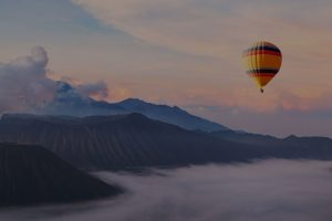 beautiful inspirational landscape with hot air balloon flying in the sky