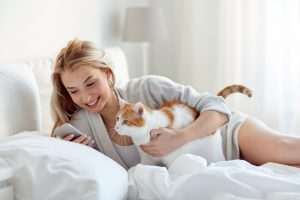 happy young woman with cat and smartphone texting message in bed at home