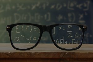 hipster glasses on a wooden rustic table in front blackboard with math formulas and calculation