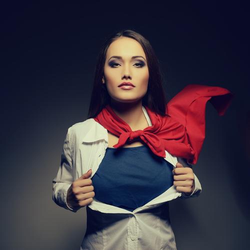 Young pretty woman opening her shirt like a superhero