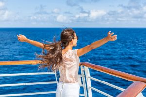 Free carefree happy girl looking at ocean with open arms in freedom pose