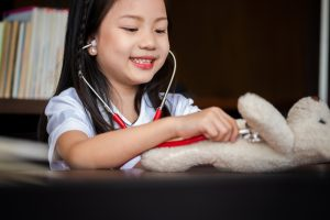 cute girl enjoys playing with stethoscope with toy